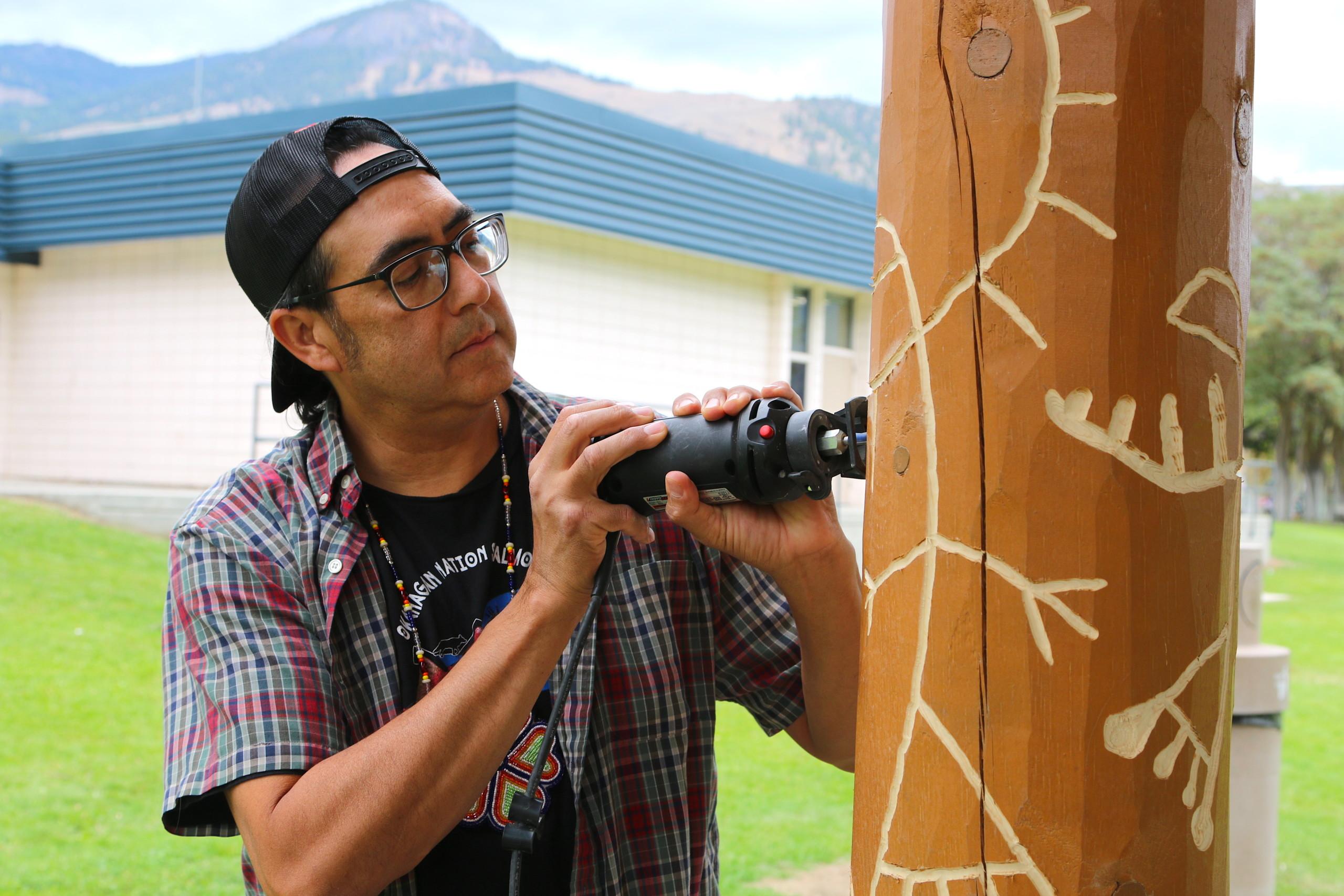 Similkameen artist carves pictographs into Similkameen Elementary School
